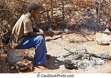 cooking dinner - outdoors traditional African kitchen, man...