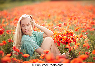 Beautiful woman on poppy flower field - Lovely woman sitting...