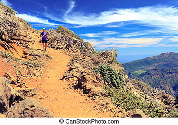Trail runner woman, walking in mountains