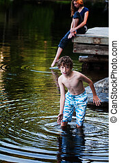 boy playing in a lake - young boy playing in a lake in...