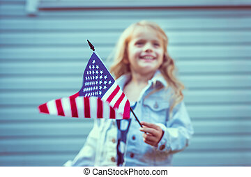 Flying american flag in little girl%u2019s hand. Selective...