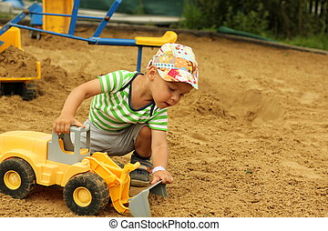 Little boy in the sandbox. - Little boy playing with...