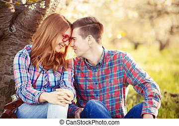 Young teen couple in the spring blossom apple trees garden