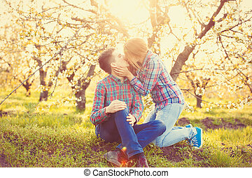 Young teen couple kissing in the spring blossom apple trees...
