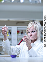 Closeup of a female researcher holding test tubes while...