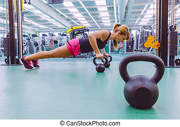 Woman doing pushups over kettlebells in crossfit training -...