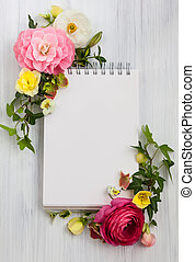 Flowers and notepad - Blank notepad and flowers over white...