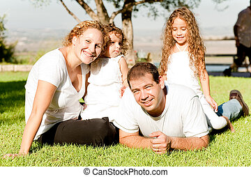 Family of four lying in grass