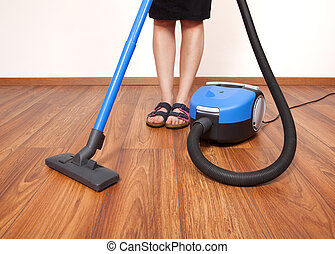 Floor cleaning - Woman cleaning the floor with vacuum...
