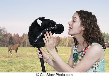 Woman Stick Horse - Woman talking to a toy stick horse