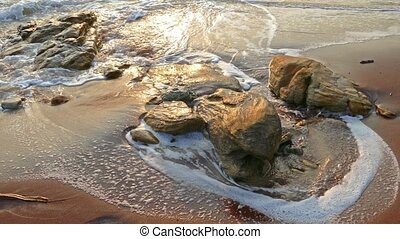 ocean shore with purple granite sand at sunset
