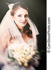 Fashion model with bridal bouquet drinking champagne and...