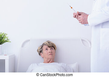 Doctor holding syringe going to do injection