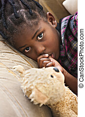 my teddy friend - African girl with plaits resting on the...