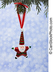 Santa Ornament - A santa ornament hanging from a tree on a...