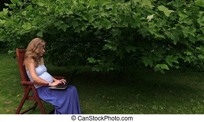 woman laptop garden - young pregnant woman work with laptop...