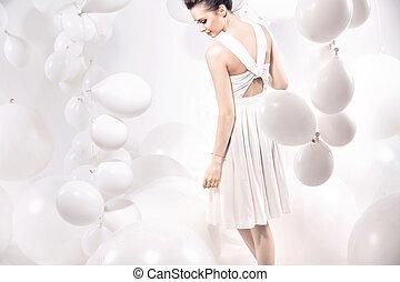 Fashion shot of a young woman among balloons