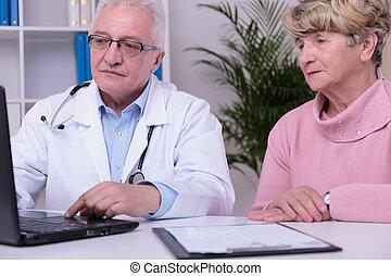 Doctor using laptop - Modern doctor using laptop during...