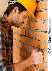 Carpenter in despair. Side view of depressed young man in...