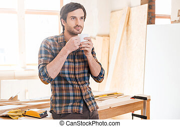 Cup of coffee for good work Thoughtful young male carpenter...