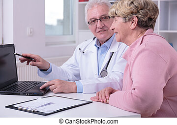Practitioner and patient looking at laptop screen