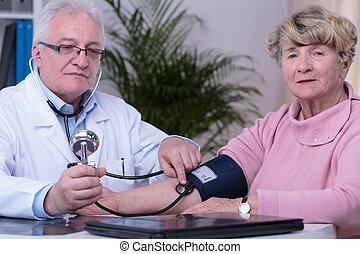 Elder woman controlling blood pressure during visit at...