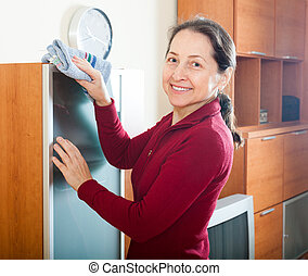 mature woman dusting furniture at home