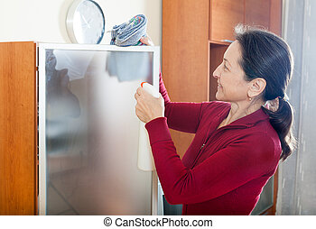 Woman cleaninig at home - Happy mature housewife dusting...
