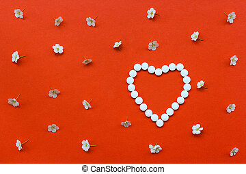 Heart shape made of white pills with white flowers pattern on orange background.Useful as background for medicine, pharmacy, prescription, homeopathy