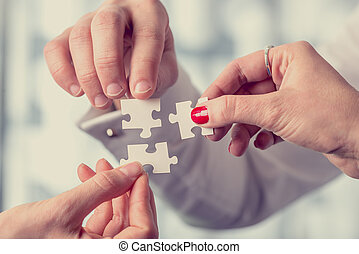 Different people matching three puzzle pieces - Hands of...