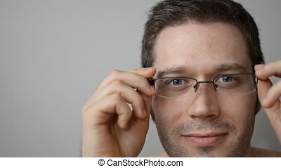 Man putting on glasses.