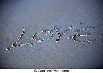 Necessary word - The word love is written by someone on sand...