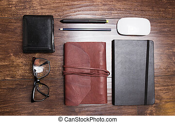 Notepads in leather cover with pencils and eyeglasses on wooden background