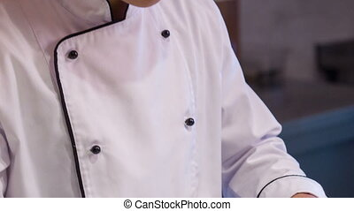 Vertical dolly shot of smiling and satisfied Asian chef -...