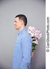 Happy man hiding flower behind his back - Side view portrait...