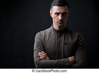 Confident young man with arms folded standing over black...