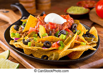 Nachos Supreme - A plate of delicious tortilla nachos with...