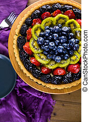 Fruit tart - Fresh fruit tart on cake stand on wood table.
