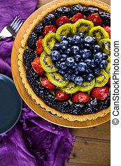 Fruit tart - Fresh fruit tart on cake stand on wood table.