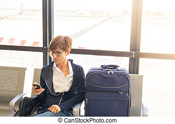 Waiting in airport terminal using phone - Businesswoman...