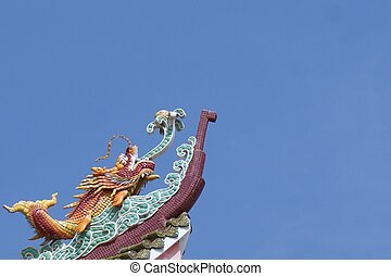 dragon fish stucco on the rooftop with blue sky background