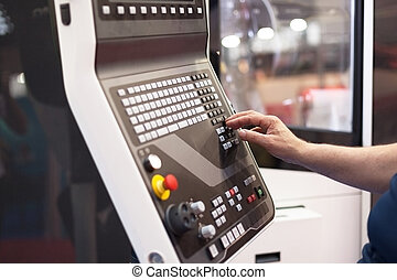 Man working at programmable machine - Hand on the control...