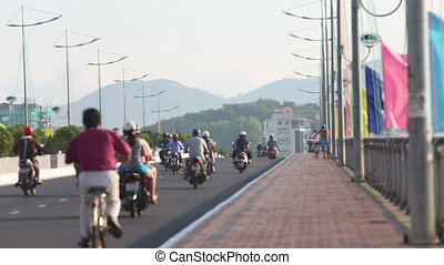 cyclists and motorcyclists drive along bridge in city -...