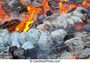 Potatoes baking in a bonfire - Baked potatoes covered with...