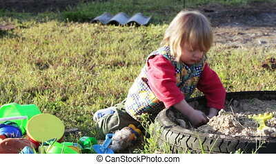 Girl with old doll - In sandbox girl playing with an old...