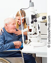 Old Man At The Ophthalmologists - Young helpful doctor with...