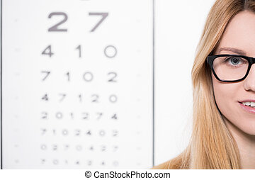 Woman and snellen chart - Young woman in glasses in front of...