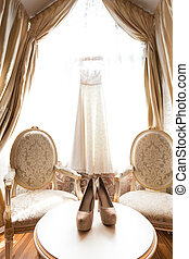 Wedding shoes and bridal dress in luxurious room