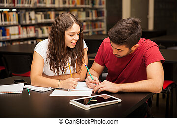 Couple studying together - Good looking young Hispanic...