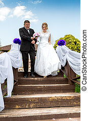 Father leading happy bride to wedding altar down the stairs...